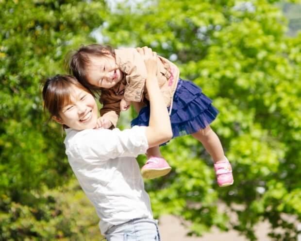 笑顔で子どもを抱き上げる女性