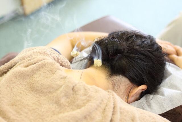 首に灸頭鍼を受ける女性